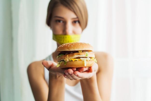Dieta, ritratto donna vuole mangiare un hamburger ma bloccato bocca skochem, il concetto di dieta, cibo spazzatura, forza di volontà nella nutrizione