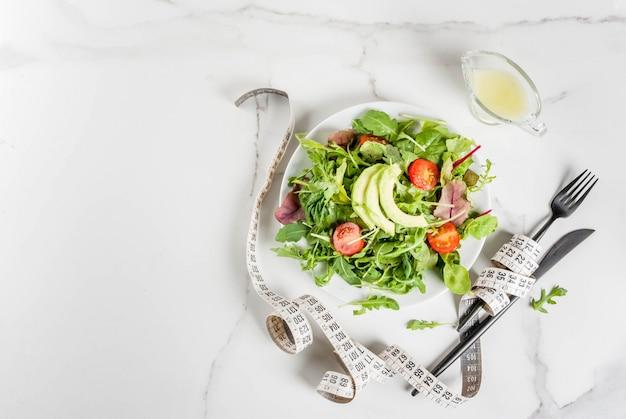 Dieta sana ed equilibrata, perdita di peso, conteggio delle calorie. piatto con foglie di insalata verde, pomodori, avocado con salsa di yogurt, tavolo bianco, con forchetta, coltello, nastro di misurazione, vista dall'alto