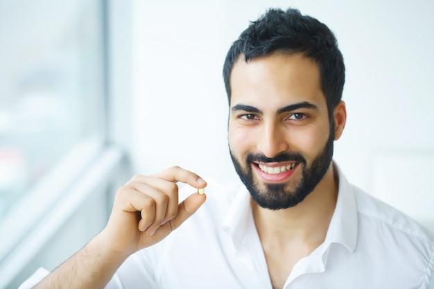 Dieta sana. nutrizione. vitamine. alimentazione sana, stile di vita. uomo con capsule di olio di pesce