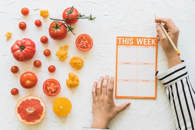 Dietista che progetta la settimana di dieta con la verdura e frutti su fondo bianco