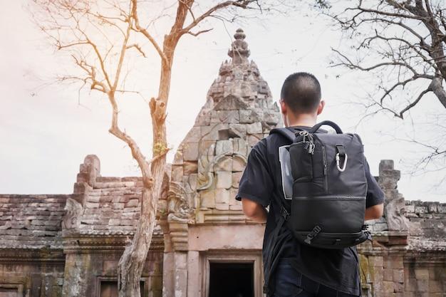 Dietro del viaggiatore con zaino e sacco a pelo asiatico del viaggiatore del giovane che sembra parco storico in tailandia