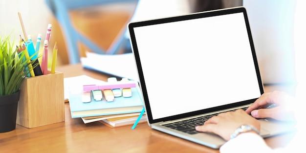 Dietro il colpo della donna creativa che lavora al computer portatile del computer con lo schermo in bianco bianco che mette sullo scrittorio funzionante di legno.