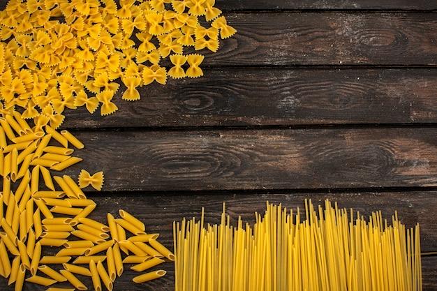 Differente giallo della pasta cruda a forma di su una tavola rustica di legno marrone