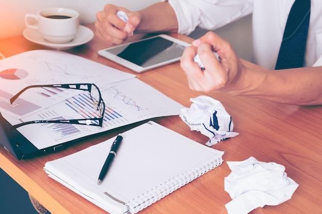 Difficile pensare all'analisi nel lavoro. il giovane uomo asiatico di affari sta lavorando a pressione nell'ufficio luminoso.