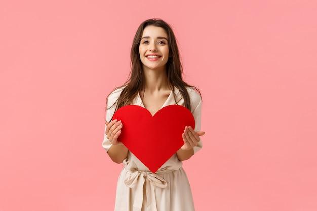 Diffondi notizie sull'amore nell'aria. la ragazza femminile dolce e tenera affascinante vuole l'amica di sorpresa con la data di sorpresa di san valentino, tenendo la carta del cuore e sorridendo, stando parete rosa