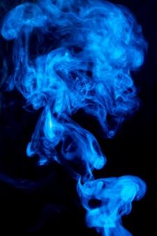 Diffusione denso fumo blu turbinio su sfondo nero