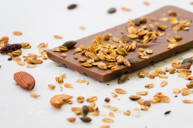 Diffusione di frutta secca sulla tavoletta di cioccolato su sfondo bianco