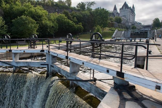 Diga sul canale rideau con parliament building sullo sfondo, parliament hill, ottawa, ontario, ca