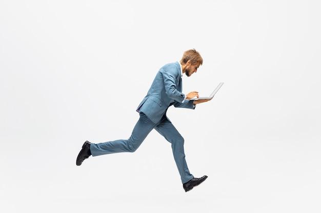 Digitando. uomo in abiti da ufficio in esecuzione, fare jogging su uno spazio bianco come atleta professionista, sportivo. ricerca insolita di uomo d'affari in movimento, azione con la palla. sport, stile di vita sano, creatività.