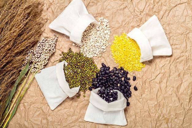 Digitare fagioli e lenticchie nel sacco su sfondo di carta marrone, miglio, fagiolo verde, soia, fagiolo nero
