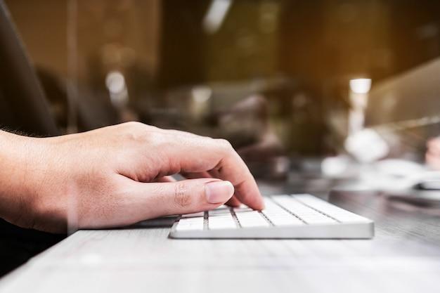 Digitazione a mano su una tastiera wireless con separatore in plexiglass acrilico impostato sulla scrivania dell'ufficio