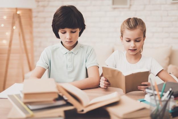 Diligent smart kids reading alla scrivania di casa.