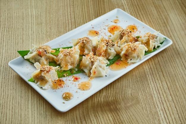 Dim sum con pollo, maiale o frutti di mare su un piatto di ceramica bianca con salsa agrodolce su superficie di legno