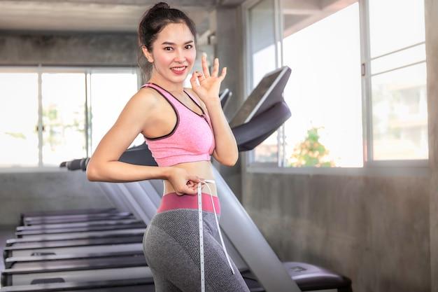 Dimagrisca la donna asiatica in nastro di misurazione della tenuta degli abiti sportivi intorno ai suoi wais alla palestra di forma fisica.