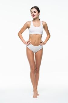 Dimagrisca la ragazza abbronzata nella posa bianca della biancheria isolata sulla parete bianca. concetto di bellezza e cura del corpo