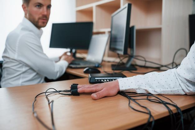 Dimmi si o no. l'uomo sospettoso passa alla macchina della verità in ufficio. fare domande. test del poligrafo