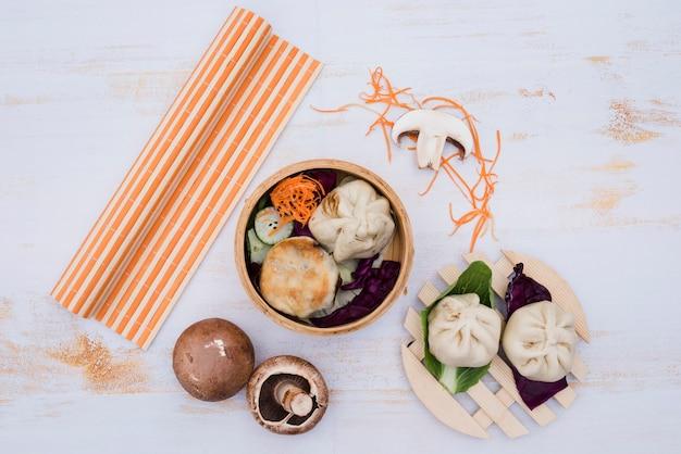Dimsum cotto a vapore cinese nella cucina tradizionale dei contenitori di bambù sulla tavola di legno bianca