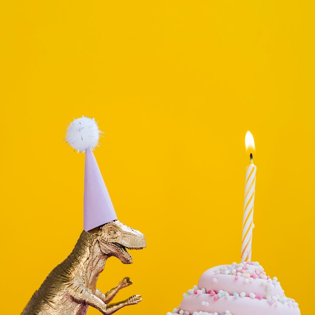 Dinosauro con cappello compleanno e delizioso muffin