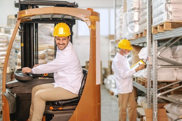 Dipendente guida carrello elevatore in magazzino.