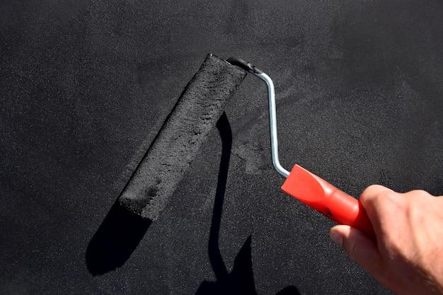 Dipingendo la superficie in nero con un rullo a pennello. la mano dell'uomo tiene il rullo a pennello.