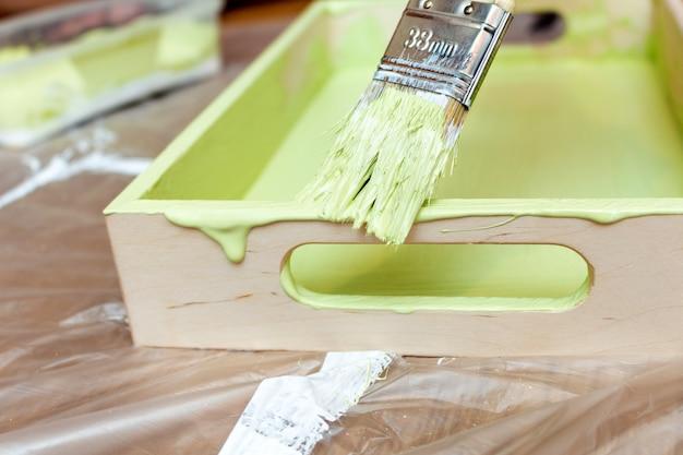 Dipingere un vassoio di legno in un primo piano verde cachi di colore