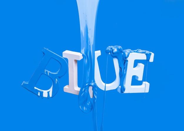 Dipingi gocciolare sulla parola galleggiante blu
