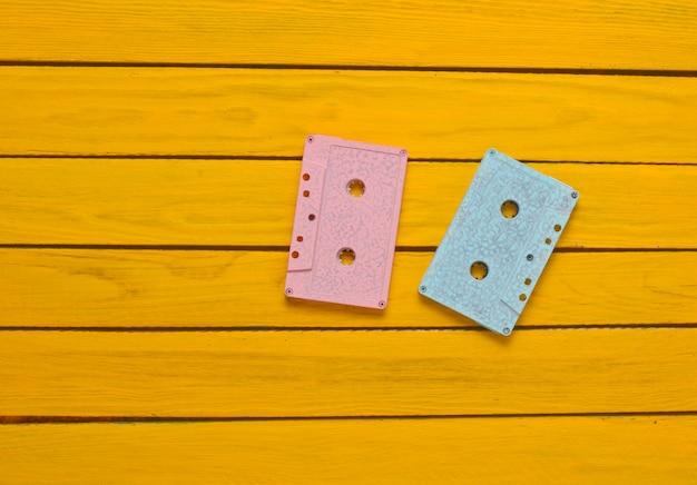 Dipinto in una cassetta audio di colore pastello blu rosa su uno sfondo di legno giallo. tecnologia audio retrò.