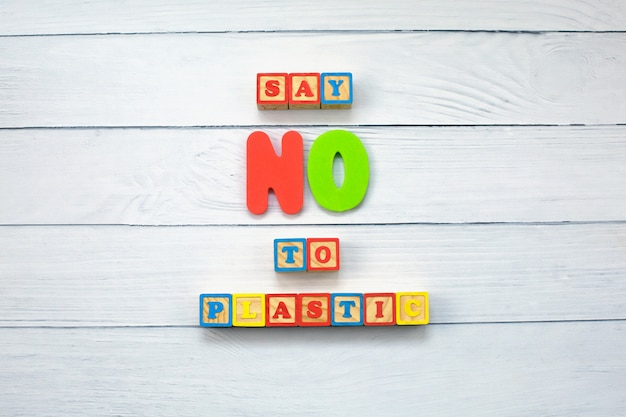 Dire di no alla plastica sui cubi di legno su fondo di legno.