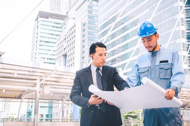 Direttore aziendale e progetto di riunione dell'ingegnere al cantiere