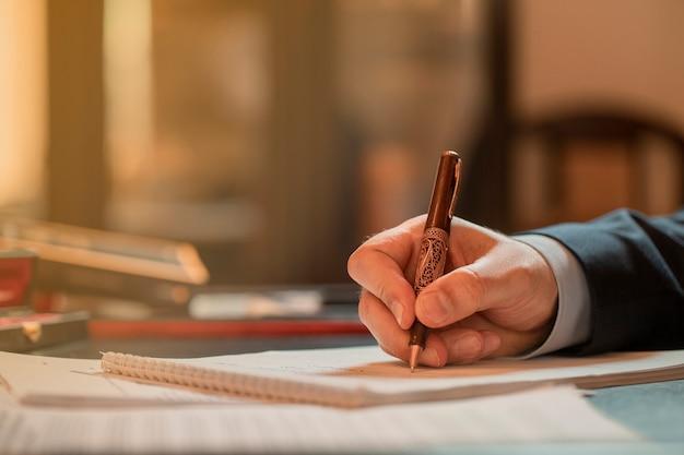 Direttore che firma i documenti con una penna di moda. foto di alta qualità