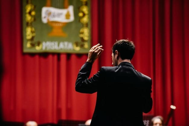 Direttore d'orchestra da dietro dirigere i suoi musicisti durante un concerto.
