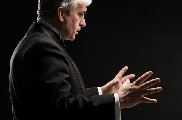 Direttore d'orchestra maschile che dirige con le mani in concerto