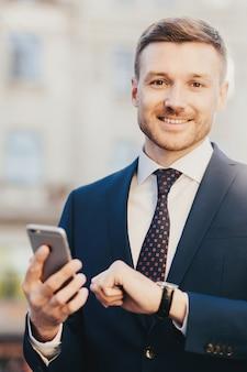 Direttore manager sorridente con orologio sul braccio, vestito elegantemente