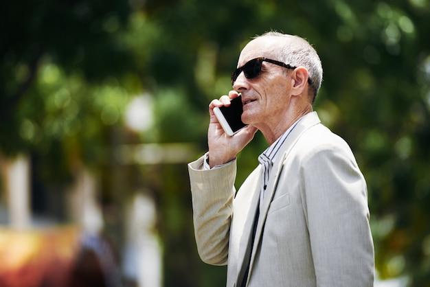 Dirigente caucasico di mezza età in occhiali da sole che parla sullo smartphone in via