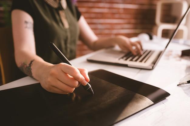 Dirigente che lavora allo stilo mentre si utilizza il computer portatile in ufficio