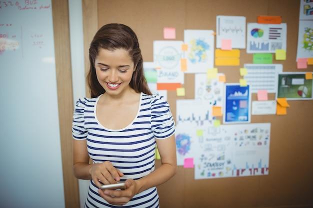 Dirigente femminile che utilizza telefono cellulare nell'ufficio
