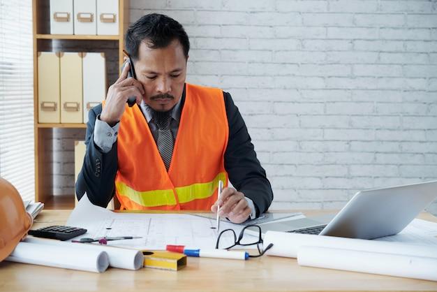 Dirigente maschio asiatico della ditta di costruzioni che si siede nell'ufficio e che parla sul telefono