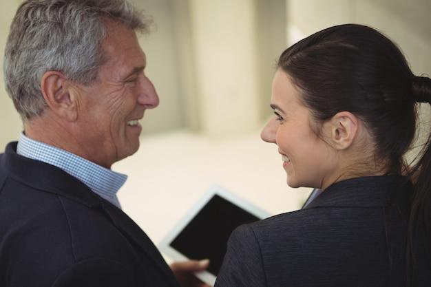 Dirigenti aziendali che sorridono mentre si guardano l'un l'altro