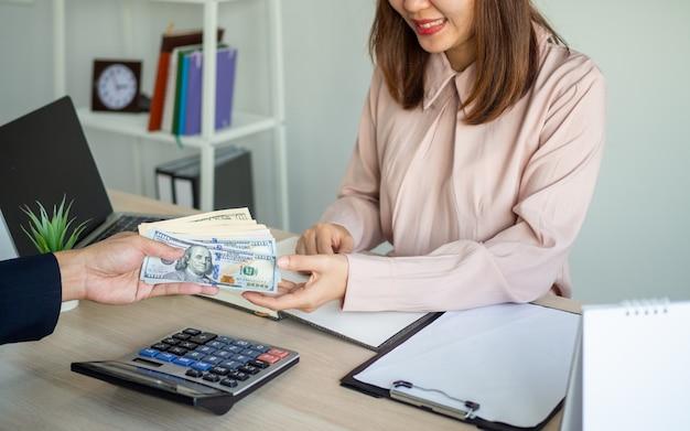 Dirigenti che forniscono stipendi per il giovane staff asiatico. ricezione di bonus annuali per dipendenti stipendiati