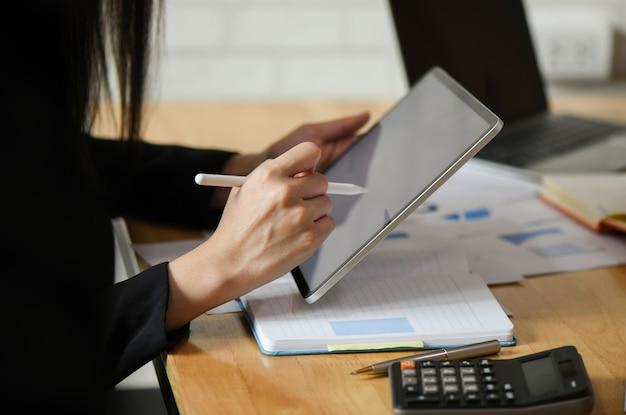 Dirigenti donne utilizzano una penna di registrazione sul tablet.