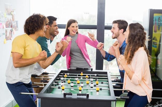 Dirigenti felici che incoraggiano mentre giocano a calcio balilla