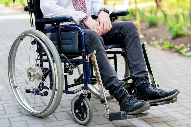 Disabile in sedia a rotelle per strada un giovane ragazzo in sedia a rotelle