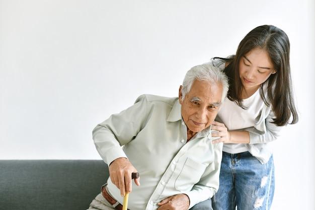 Disabilitare e ferire l'uomo asiatico senior tenta di alzarsi con il bastone da passeggio