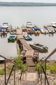 Discesa al ponte di legno e parcheggio piccole imbarcazioni e motoscafi sul fiume volga.