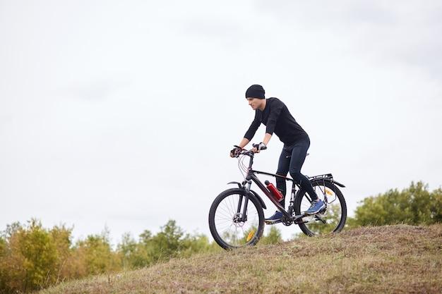 Discesa in bicicletta. equipaggia il ciclismo all'aria aperta, indossa tuta e berretto neri, trascorre il tempo libero in modo inattivo