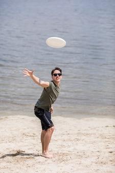 Disco di frisbee di lancio dell'uomo adulto sulla spiaggia