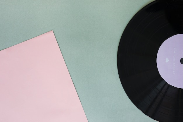 Disco in vinile nero con carta sul tavolo