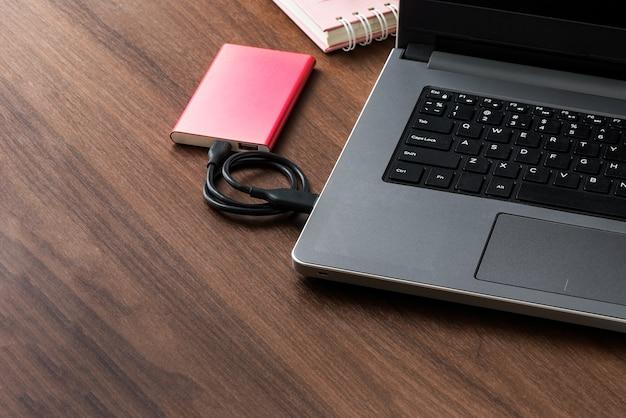 Disco rigido esterno (hdd) collegato al computer portatile per il trasferimento o il backup dei dati su desktop in legno