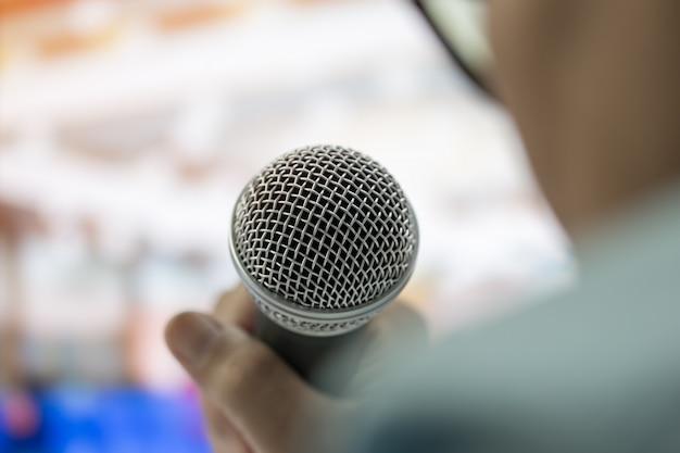 Discorso astuto della donna di affari e parlare con i microfoni nella stanza di seminario o nella sala per conferenze di conversazione