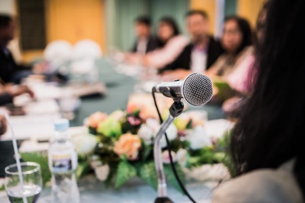 Discorso di altoparlante imprenditrice intelligente e parlando con microfoni in sala riunioni per la conferenza di riunione